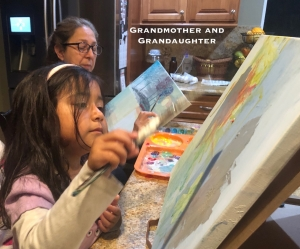 Grandmother & granddaughter painting together.